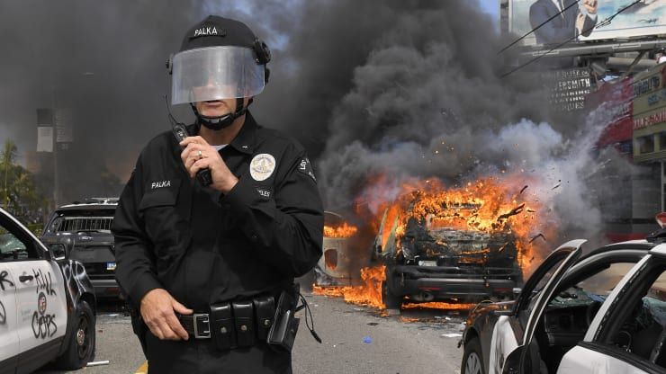 Los Angeles Police Department commander Cory Palka stands among several destroyed police cars ...jpg